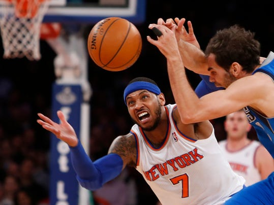 New York Knicks' Carmelo Anthony (7) fights for possession against Dallas Mavericks' Jose Calderon during the first half of an NBA basketball game, Monday, Feb. 24, 2014, in New York.  (AP Photo/Jason DeCrow)