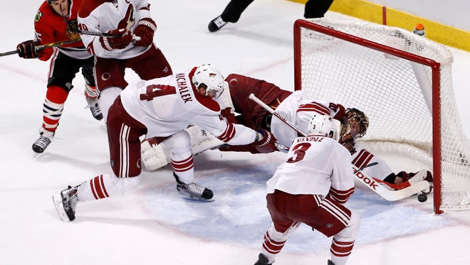 Arizona Coyotes goalie Mike Smith (41) makes a save on a shot by Chicago Blackhawks center Andrew Shaw (left) before the puck completely crossed the goal line as Shane Doan (19), Zbynek Michalek (4), and Keith Yandle also defend during an overtime period Monday, Feb. 9, 2015, in Chicago. The play was reviewed and confirmed a no goal as the Coyotes went on and won in a shootout period 3-2.