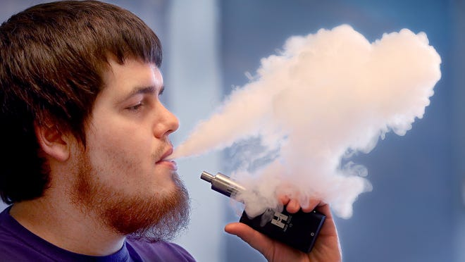 Indy Vapor Shop, the first vapor store in Indianapolis at 4930 Lafayette Road. E-cigarettes or vapes, as they are also called, are under attack. Opponents of these largely unregulated products point to statistics that show that teens have embraced these products, which come in flavors like bubble gum and candy cane that seem designed for the youth sweet tooth. Here Josh Maynard, employee at Indy Vapor Shop, takes a break to smoke his e-cigarette.
