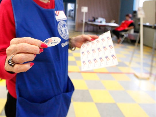 Volunteer handing out I Voted stickers after filling