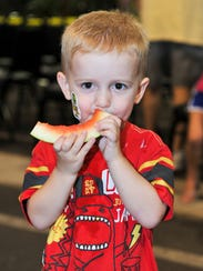 Peyton Watkins, 3, munches on watermelon during the