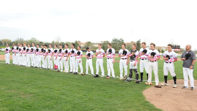 The Plymouth Wildcats, wearing special uniforms in support of Mother's Day and breast cancer awareness, line up before Wednesday's opening game.