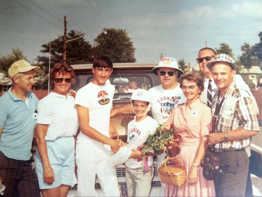 Corning Soap Box Derby 1966 champion Jack Littleton, holding flowers, shakes hands with 1965 winner Joey Dudick. On the left are Dudick's parents and on the right are Littleton's parents. Race Director Frank Hamm, wearing the pith helmet, and sponsor Jim Fuller are in the back.