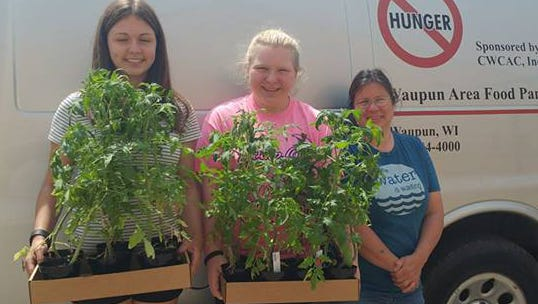 Waupun Food Pantry and Community Garden coordinator, Terri Respaljie (right) accepts some of the more than 400 tomato plants grown by the Waupun Ag Ed students. Making the presentation are FFA members Brianna Asmus (left) and Roni Schulz.