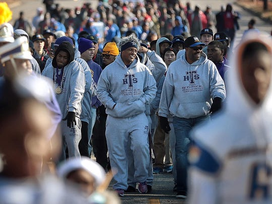 Trezevant High School Coach Teli White leads his team down Central Avenue during the Parade of Champions put on by the City of Memphis to honor players from East, Lausanne, Trezevant and Whitehaven high schools who all won their respective football championships.