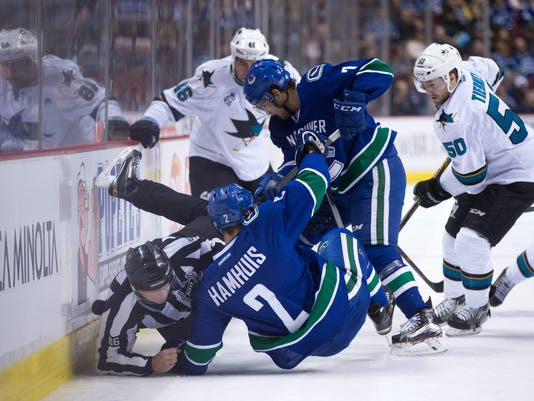Linesman Brad Lazarowich, left, collides with Vancouver Canucks' Dan Hamhuis (2) as Linden Vey (7) digs for the puck against San Jose Sharks' Chris Tierney (50) and Roman Polak (46), of the Czech Republic, during the first period of an NHL hockey game, in Vancouver, British Columbia, on Sunday, Feb. 28, 2016. (Darryl Dyck/The Canadian Press via AP) MANDATORY CREDIT
