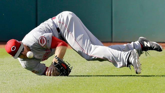 Cincinnati Reds' Brennan Boesch dives for but cannot hold on to a single hit by Cleveland Indians' Jason Kipnis in the sixth inning of a baseball game, Saturday, May 23, 2015, in Cleveland.