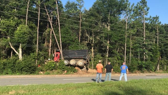 A dump truck appears to be caught behind trees and a power pole on Highway 87.