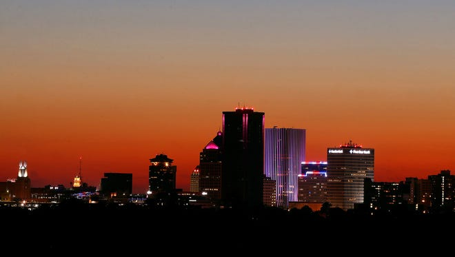 The sun sets behind the skyline in downtown Rochester, as seen from Cobbs Hill Park near the reservoir.
