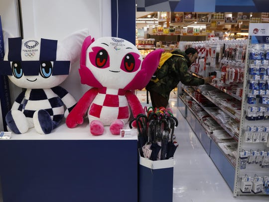 In this Jan. 8, 2020, file photo, dolls of the Tokyo Olympic and Paralympic mascots, Miraitowa and Someity, are on display at a Tokyo 2020 official shop in the Shinjuku district of Tokyo. Official Tokyo Olympic souvenir shops are drawing few customers these days. The pandemic and the fact the Olympics have been postponed for a year has wiped out almost all business.