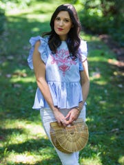 Christine Donnelly wears a blue and white blouse with red embroidery by SheIn.com with white raw hem denim jeans from Anthropologie and tan suede espadrilles by Marc Fisher from Nordstrom