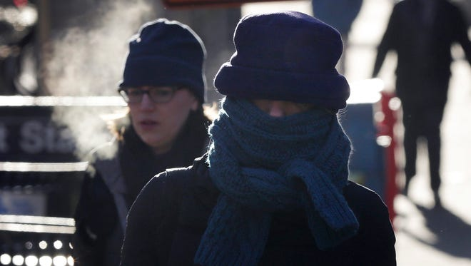A woman is bundled against the cold as she crosses Broadway in New York City on Tuesday, Feb. 24, 2015. Officials across the country say at least 70 deaths are attributable to the unusually cold and snowy weather this year.