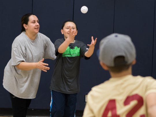 Miracles Baseball player Angel catches the ball as his mother Elvira Olivas stands by for support.