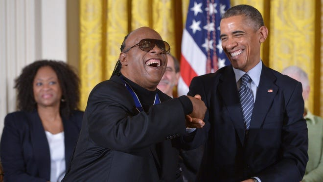 President Barack Obama congratulates Medal of Freedom recipient Stevie Wonder during a ceremony in the East Room of the White House in 2014. Wonder also made Obama's music playlist, which he released Friday.