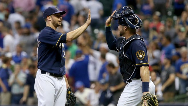 Tyler Thornburg, left, and Manny Pina celebrate after the Brewers' 2-1 win over the Chicago Cubs on Wednesday at Miller Park.