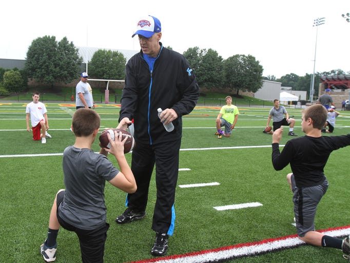 Jim Kelly works with the kids at his Jim Kelly Football Camp at St. John Fisher College in Pittsford, NY.  Kelly gives Jack LeStrange, 13, of Walworth advice on throwing.