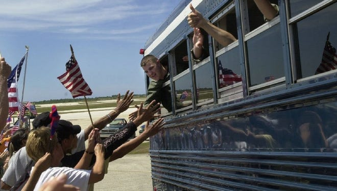 Guam residents welcome members of the U.S. spy plane's air crew who arrived at Andersen Air Force Base on Guam on board a chartered Continental Airline jet Thursday, April 12, 2001.