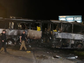 A pair of California Highway Patrol Officers walk past the burned out tour bus where at least nine people died in a fiery crash between a tour bus and a FedEx truck on Interstate 5 Thursday, April 10, 2014, in Orland, Calif.