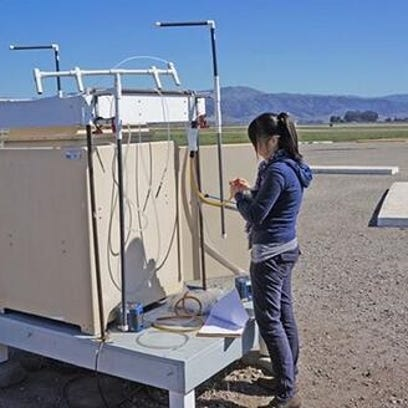 An employee of the Department of Pesticide Regulation reviews a monitoring device set up at the Salinas Airport.