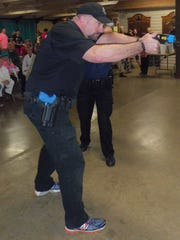 File - Manitowoc Police Department Patrol Officer Jason Wilterdink demonstrates use of a Taser during Crime Prevention Day.