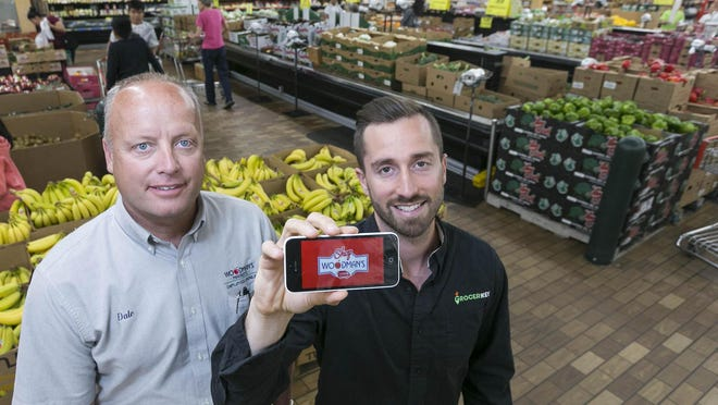 Jeremy Neren (right), founder and CEO of GrocerKey, shows the app in 2015 with Woodman's store manager Dale Martinson as the companies were beginning work on Woodman's online grocery service.