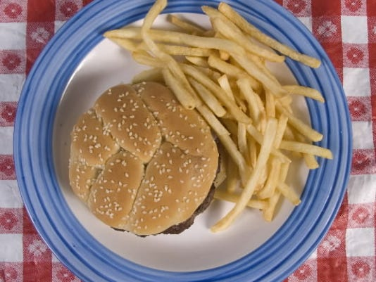 Indulge in a weekend meal, but one is enough. Don't gorge yourself on fatty foods until Monday. Daily Record/Sunday News - File