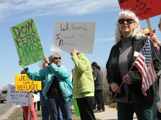 People attending a rally welcoming immigrants to America display signs and flags Saturday along East Main Street in front of the Farmington Museum at Gateway Park.