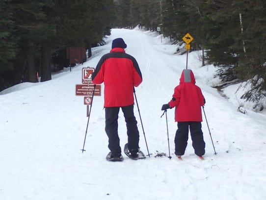 A grandfather and grandson ski the nearby Going to