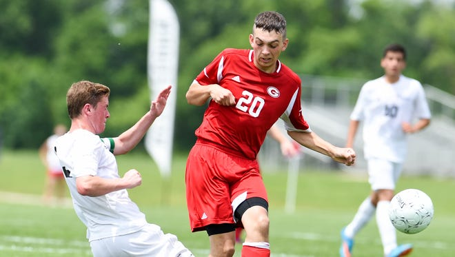 Gilbert's Schuyler Hop (20) attempts to move the ball down field but looses the ball as St. Albert's Martin Shudak (3) slides in to defend on Friday, June 5, 2015, during the 2015 Boys State Soccer Championship held at the Cownie Soccer Park.