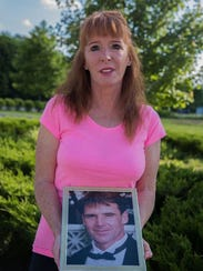 Lawyer Patricia Rouse holds a photo of her brother
