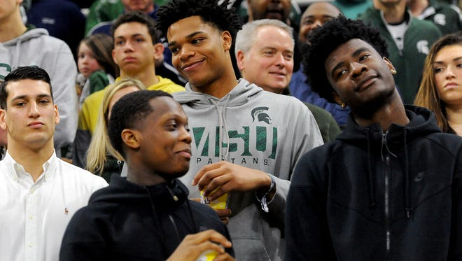 Michigan State basketball commits Miles Bridges, center, in gray, and Cassius Winston, front left, stand with MSU recruit Josh Jackson, the nation's top-ranked recruit, in the lower bowl of the Breslin Center Saturday, March, 5, 2015, during the Spartans' 91-76 win over Ohio State.