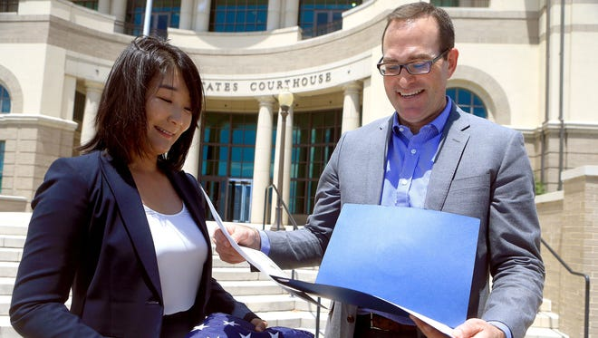 Judge Young Min Burkett of Corpus Christi Municipal Court and her husband, Nathan Burkett, hold her citizenship papers July 7, 2017, after she was sworn in as a U.S. citizen at the federal courthouse in Corpus Christi.