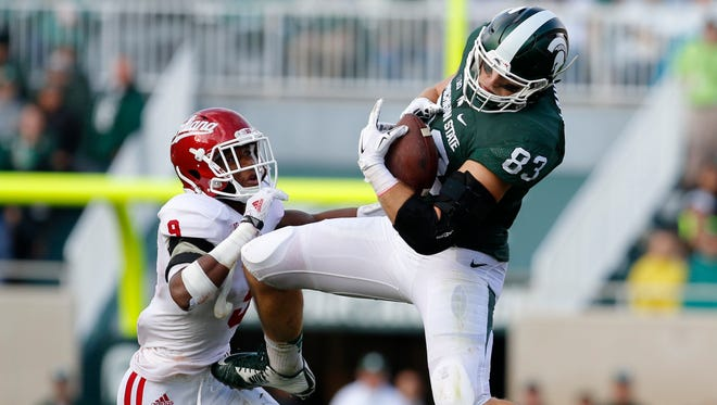 Michigan State's Paul Lang (83) catches a pass against Indiana's Jonathan Crawford during the second quarter of an NCAA college football game, Saturday, Oct. 24, 2015, in East Lansing, Mich.