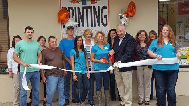 Merita Hensley (center, with scissors) celebrates the grand opening and ribbon cutting for AdPro Promotional Products in Mars Hill.