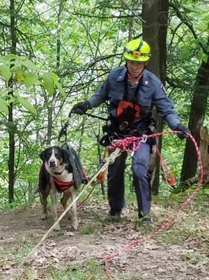 """State Parks Police Officer Ryan Clancy escorts """"Skippy"""" just after using a harness and ropes to rescue the dog Monday in Letchworth State Park."""