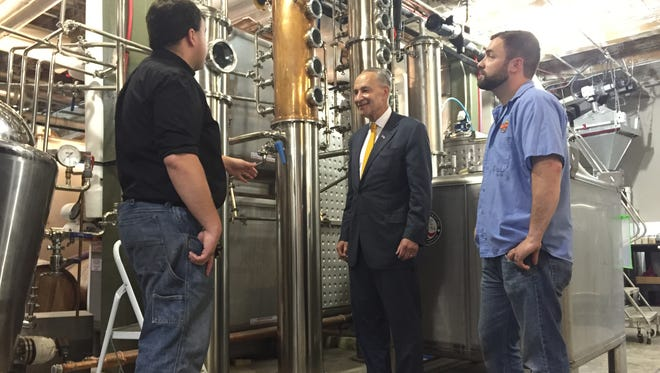 U.S. Senator Charles Schumer visits Black Button Distilling, 85 Railroad St., on Monday, with owner Jason Barrett, left, and Dan Western, co-owner of Lost Borough Brewery.