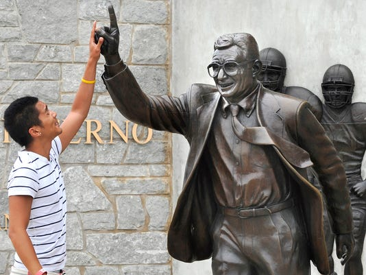 Joseph Jacobo, a senior at Penn State University, places his hand on the hand of the statue of Joe Paterno before having his photo taken.