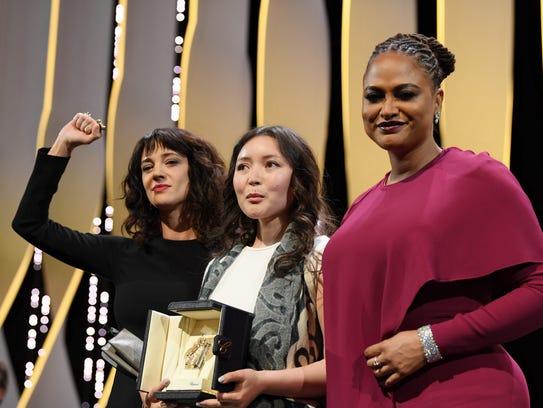 Asia Argento, left, raises her arm as actress Samal
