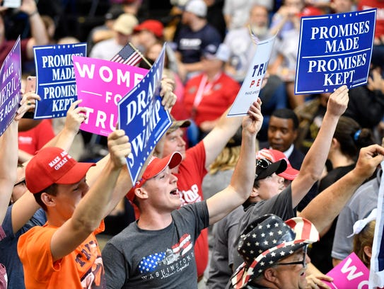 Supporters hold signs before the rally by President