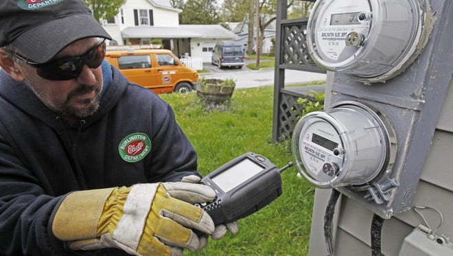 """In this May 10, 2012 file photo, Mark Delbeck, of Burlington Electric, checks the radio frequency of a newly-installed """"smart"""" meter in Burlington, Vt. Home efficiency measures such as installing new windows or replacing insulation may actually cost homeowners money in the long run, according to the surprising conclusion of a University of Chicago study released Tuesday, June 23, 2015."""