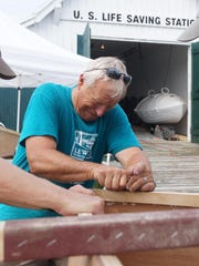 Bob Hyberg planes the bottom of a skiff's hull during Family Boat Building Weekend in Lewes on Saturday.