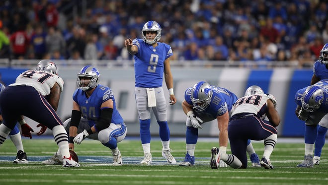 Lions quarterback Matthew Stafford points out the Patriots defense to center Travis Swanson in the second quarter at Ford Field on Aug. 25, 2017 in Detroit.