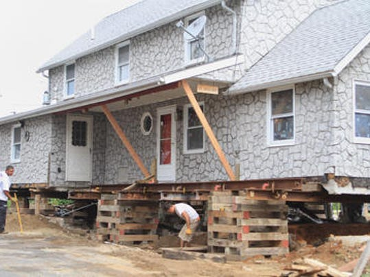 Laborers work on raising a home in Highlands in August 2013. (Asbury Park Press file photo)