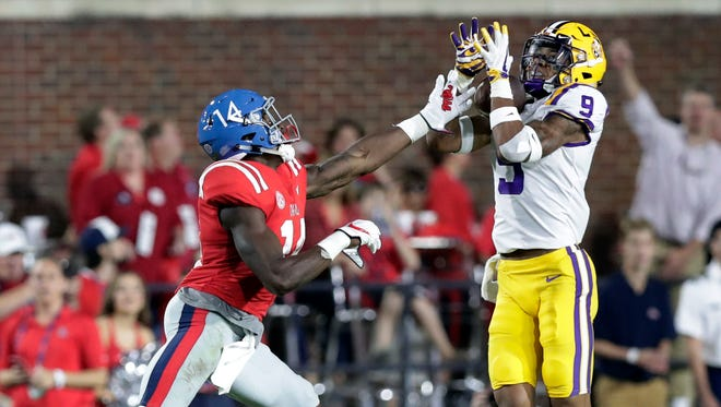 LSU safety Grant Delpit (9) intercepts a pass intended for Mississippi wide receiver D.K. Metcalf (14) in the first half of an NCAA college football game in Oxford, Miss., Saturday, Oct. 21, 2017.