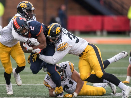 Illinois running back Reggie Corbin is tackled by Iowa's