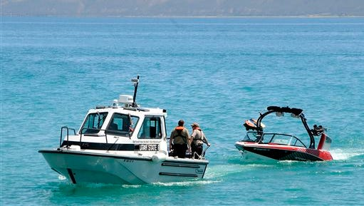 Responders tow a boat to the Bear Lake State Park Marina, Tuesday, June 2, 2015 near Garden City, Utah. The boat capsized in a storm on Monday and four people died as a result of the accident. (Eli Lucero/The Herald Journal via AP)