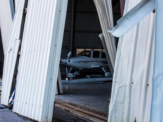 A plane sits in a hangar damaged by Hurricane Irma