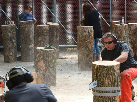 Mahesh Nepal (lower left) watches the depth of a chainsaw