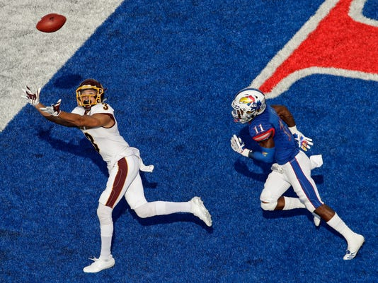 Central Michigan wide receiver Mark Chapman (3) stretches for but misses a pass under pressure from Kansas safety Mike Lee (11) during the first half of an NCAA college football game, Saturday, Sept. 9, 2017, in Lawrence, Kan. (AP Photo/Charlie Riedel)