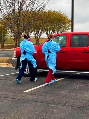 Nurses approach a vehicle during a drive-thru coronavirus testing site in Ardmore on Thursday. More than 100 people were tested in the Ardmore Convention Center parking lot.